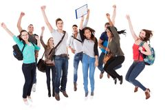 Successful university students over white background. Full length portrait of successful university students with arms raised jumping over white background stock photography