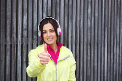Successful urban female athlete. Doing thumbs up gesture. Sporty positive fitness woman wearing sport outfit and headphones Stock Photo