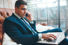Successful usinessman working in office. Successful businessman working in office, looking at laptop screen, talking on phone. Business, success concept Royalty Free Stock Image