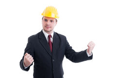 Successful and victorious engineer, architect or contractor. Wearing suit, tie and yellow hardhat Royalty Free Stock Photos