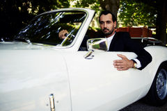 Successful and wealthy businessman sitting behind the wheel of his luxury cabriolet car on countryside road. Confident handsome man with depth look sits in his Royalty Free Stock Photo