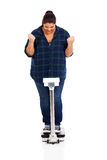 Successful weight loss. Cheerful overweight girl on scale successful weight loss Royalty Free Stock Images