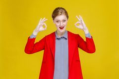 Successful well dressed red head business woman  showing ok sign. Studio shot, isolated on yellow background Royalty Free Stock Photo