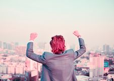Successful Western businessman with hands up looking at the city stock images