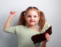 Successful winner kid girl holding wallet with much money on blu. E background Stock Images