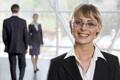 Successful woman. Smiling Caucasian businesswoman in eyeglasses and two walking businesspeople on the background Stock Image