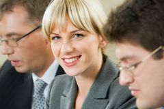 Successful woman. Successful young business woman with charming confident smile between two co-workers stock images