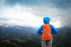Woman backpacker enjoy the view face the snow capped mountain. Successful woman backpacker enjoy the view face the snow capped mountain Royalty Free Stock Images