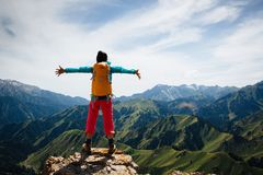 Woman backpacker enjoy the view on top of mountain rock Royalty Free Stock Images