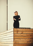 Successful woman in business clothes standing near the building. Looking away Royalty Free Stock Image