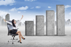 Successful woman on chair and business graph Royalty Free Stock Image