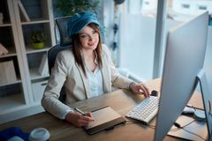 Successful woman is devoted to her career and working late on co. Successful casual woman is devoted to her career and working late on computer at office royalty free stock images