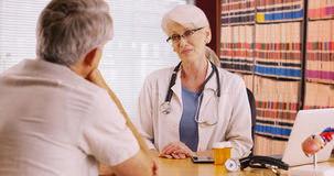 Successful woman doctor talking with patient in her office Stock Photography