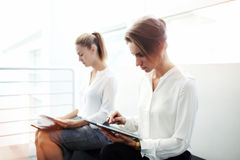 Successful woman entrepreneur working on touch pad while her partner reading paper documents before conference, Royalty Free Stock Photos