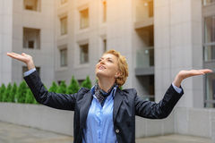 Successful woman is grateful for her achievement. Finally success. Happy young businesswoman is raising arms and looking up with gratitude. She is standing near Stock Photos