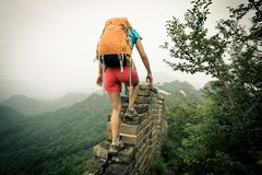 Woman hiker climbing up on the top of great wall stock images