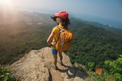 Woman hiker stand on mountain peak cliff edge. Successful woman hiker stand on mountain peak cliff edge Stock Images