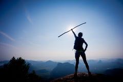 Woman hiker stand on sunrise mountain peak rock edge. Successful woman hiker stand on sunrise mountain peak rock edge Royalty Free Stock Photo