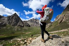 Woman hiker use smartphone in mountain top rock. Successful woman hiker use smartphone in mountain top rock Stock Images