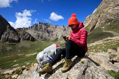 Woman hiker use smartphone in mountain top rock. Successful woman hiker use smartphone in mountain top rock Royalty Free Stock Image