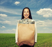 Successful woman holding bag with money. Excited successful woman holding bag with money over blue sky and green field Royalty Free Stock Photography
