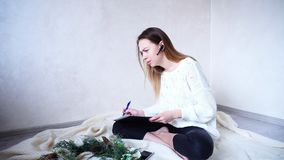 Successful Woman photographer arranges meetings on bluetooth hea. Sweet female professional photographer talks to customer and specifies details of New Year`s Stock Photography
