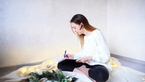 Successful woman photographer arranges meetings on bluetooth hea. Sweet female professional photographer talks to customer and specifies details of New Year`s Stock Image