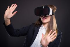 Successful woman playing game and watching video. In virtual reality and gesturing with hands rised up Stock Photos