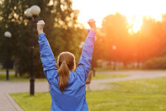 Successful woman runner raising arms to the sun. Stock Photography