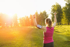 Successful woman runner raising arms to the sun. Stock Image
