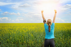 Successful woman runner raising arms to the sun. Royalty Free Stock Image