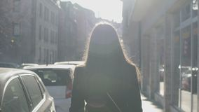 Successful woman slowly walking down street, bright sun beams illuminating her. Stock footage stock video