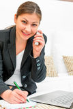 Successful woman in a suit talking on the phone. And making notes in a notebook Royalty Free Stock Photos