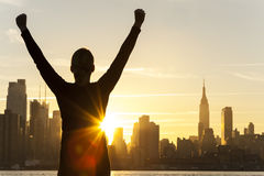 Successful Woman Sunrise New York City Skyline. Silhouette of a successful woman or girl arms raised celebrating at sunrise or sunset in front of the New York royalty free stock photo