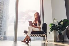Successful woman wearing suit sitting on armchair using tablet computer at her loft apartment in city center Stock Photos