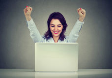 Successful woman winner with arms raised looking at laptop. Successful young woman winner with arms raised looking at laptop sitting at desk royalty free stock photography