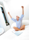 Successful woman working on bed. Woman with laptop on bed celebrating a recent win or sell online Stock Images