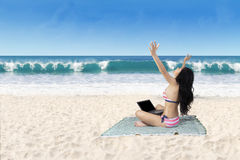 Successful woman working with laptop at beach Stock Photography