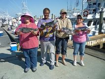 Successful Women Anglers. Photo of happy women anglers holding their trophy seabass that they caught on the morning star headboat on 6/2/11 off the coast of Royalty Free Stock Photo