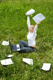 Successful work. Portrait of happy woman with papers in hands sitting on green glade and raising her arms Stock Image