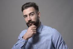 Successful young adult business man touching beard looking at camera thoughtfully. Against gray studio background Stock Photo