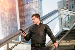Successful young adult entrepreneur texting on phone in the city office building. stock image