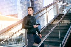 Successful young adult entrepreneur walking and  texting on phone in the city office building. royalty free stock images