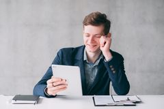 Successful young ambitious company worker. Portrait of successful, ambitious company worker. Young man using tablet at his workplace, enjoying fun content stock photos