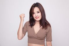 Successful  young Asian woman hold fist up. Royalty Free Stock Photo