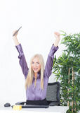 Successful young blonde businesswoman, victory gesture, hands up, smiling at office Royalty Free Stock Photos