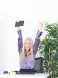 Successful young blonde businesswoman, victory gesture, hands up, smiling at office Stock Photography