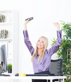 Successful young blonde businesswoman, victory gesture, hands up, smiling at office Royalty Free Stock Photo