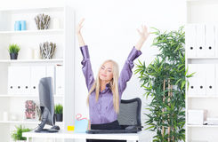 Successful young blonde businesswoman, victory gesture, hands up, smiling at office Royalty Free Stock Image
