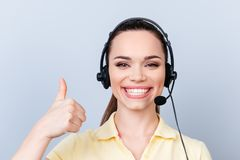 Successful young brunette girl in headset on a pure light background, wearing casual yellow tshirt, smiling and showing thumbup s stock images